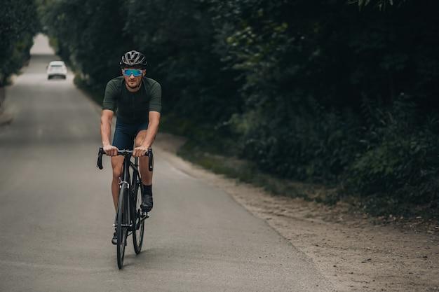 Homem caucasiano, andar de bicicleta na estrada entre a floresta.