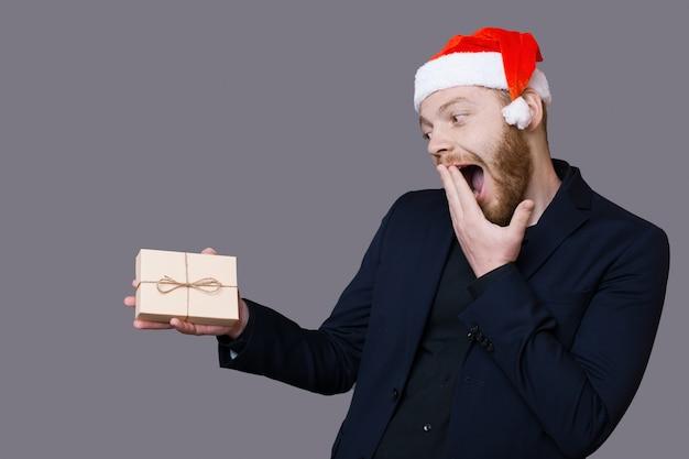 Homem caucasiano animado com barba segurando um presente e cobrindo a boca, gesticulando felicidade na parede cinza com espaço livre