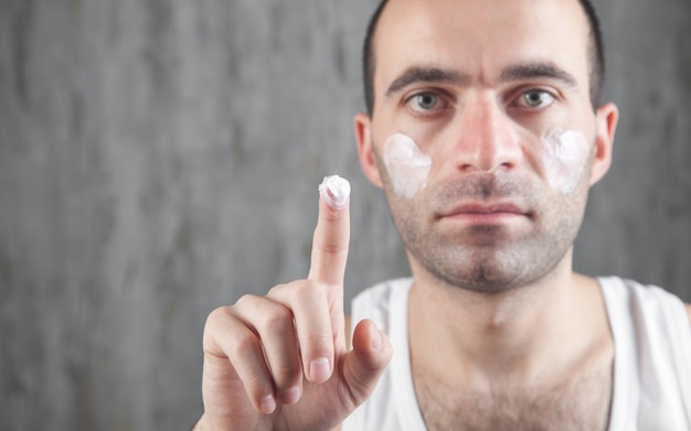Homem caucasiano, aplicando creme facial.
