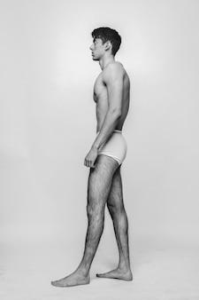 Homem caucasiano atraente com um corpo perfeito em pé de cueca