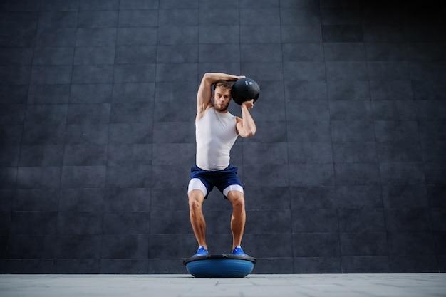 Homem caucasiano barbudo bonito muscular forte, levantamento de peso em pé na bola bosu. no fundo é parede cinza.