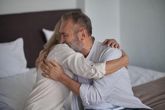 Homem caucasiano barbudo, de cabelos grisalhos, maduro, romântico, sentado na cama no quarto, abraçando a esposa
