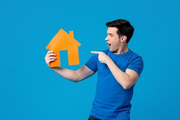 Homem caucasiano bonito animado segurando e apontando para o modelo de casa