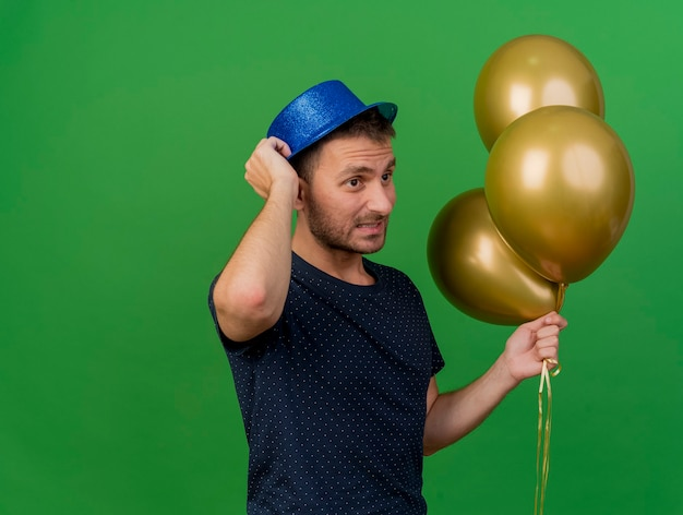 Homem caucasiano bonito ansioso com chapéu de festa azul parado de lado segurando balões de hélio isolados em um fundo verde com espaço de cópia
