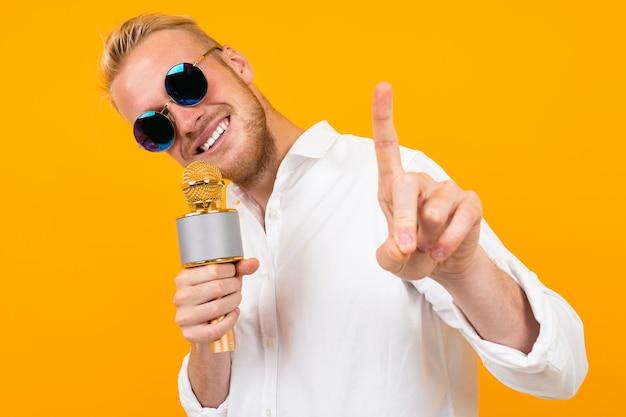 Homem caucasiano bonito com óculos canta músicas em karaoke com microfone isolado em amarelo