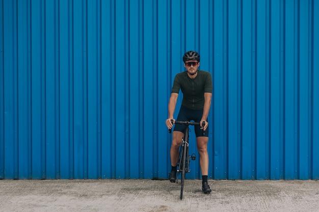 Homem caucasiano bonito com roupas esportivas, capacete e óculos, sentado na bicicleta preta sobre a parede azul. ciclista ativo fazendo uma pausa durante o treino ao ar livre.