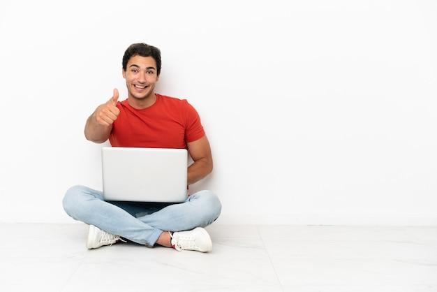 Homem caucasiano bonito com um laptop sentado no chão com o polegar para cima porque algo bom aconteceu