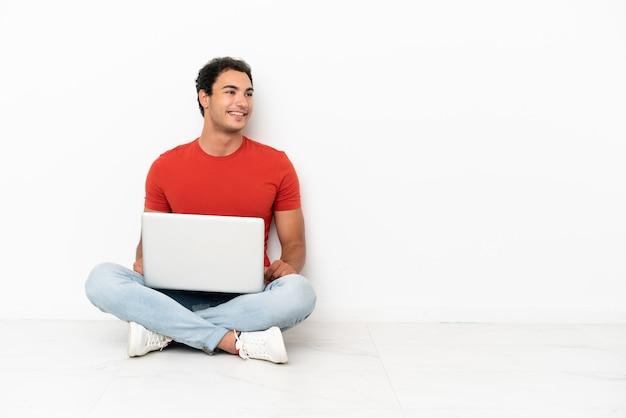 Homem caucasiano bonito com um laptop sentado no chão com os braços cruzados e feliz