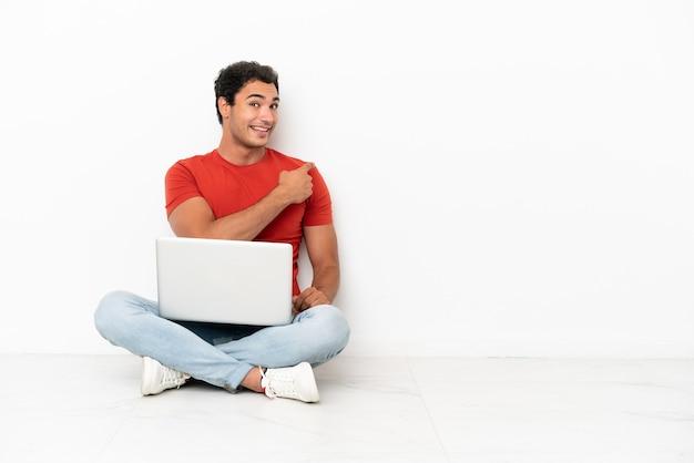 Homem caucasiano bonito com um laptop sentado no chão e apontando para trás