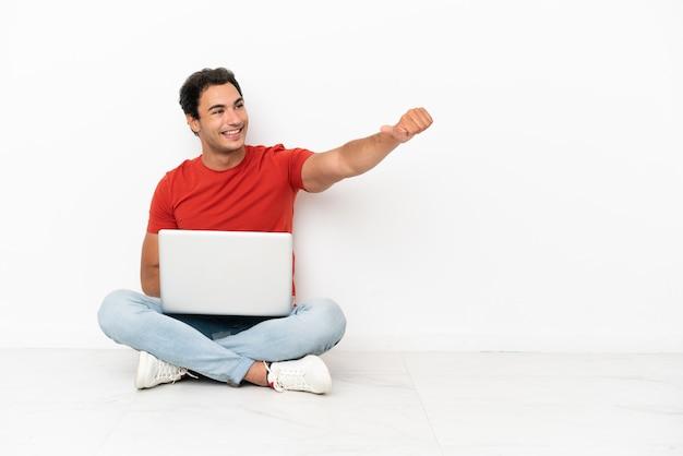 Homem caucasiano bonito com um laptop sentado no chão fazendo um gesto de polegar para cima