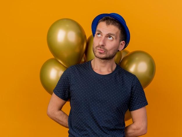 Homem caucasiano bonito confuso com chapéu de festa azul segurando balões atrás, isolado em um fundo laranja com espaço de cópia
