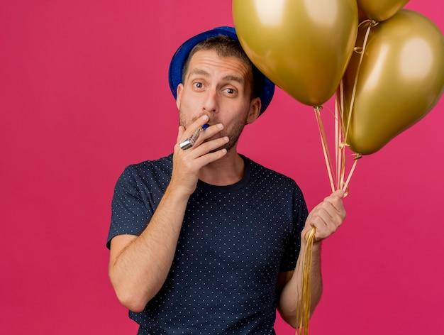 Homem caucasiano bonito e alegre com chapéu de festa azul segurando balões de hélio soprando apito isolado em um fundo rosa com espaço de cópia