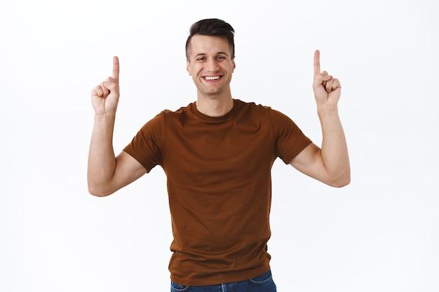 Homem caucasiano bonito e alegre em uma camiseta marrom, conselho, clique no link de cima, apontando o dedo para cima e sorrindo