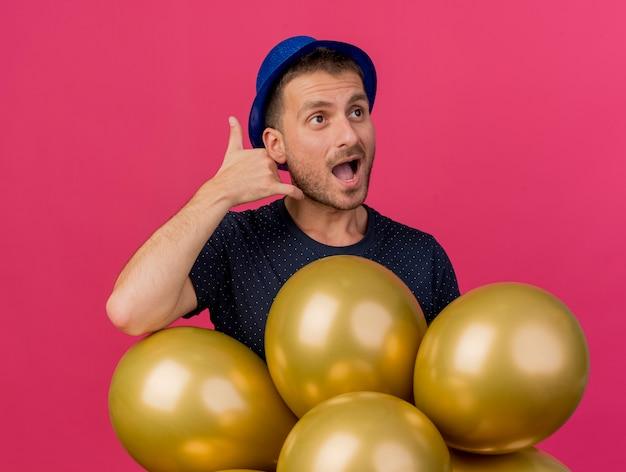 Homem caucasiano bonito e alegre usando gestos de chapéu de festa azul me chama de sinal e segura balões de hélio olhando para o lado isolado no fundo rosa com espaço de cópia