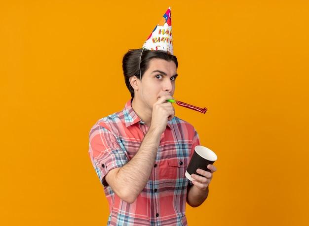 Homem caucasiano bonito e confiante usando um boné de aniversário, segurando um copo de papel e soprando um apito de festa