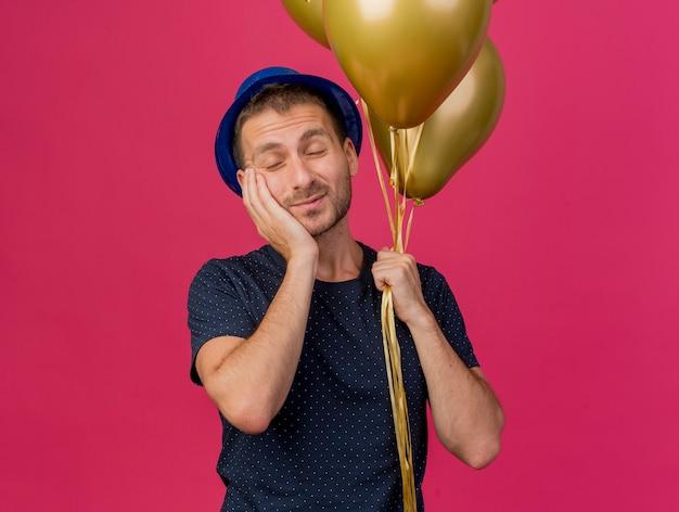 Homem caucasiano bonito e satisfeito com um chapéu de festa azul segurando balões de hélio e colocando a mão no rosto isolado em um fundo rosa com espaço de cópia