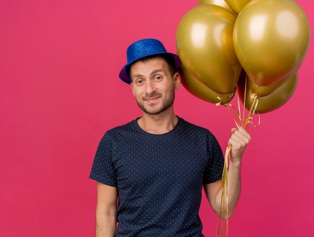 Homem caucasiano bonito e satisfeito com um chapéu de festa azul segurando balões de hélio, olhando para a câmera isolada no fundo rosa com espaço de cópia