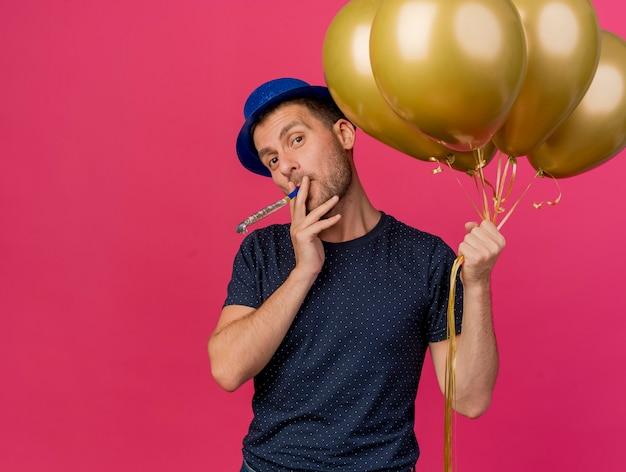 Homem caucasiano bonito e satisfeito com um chapéu de festa azul segurando balões de hélio soprando apito isolado em um fundo rosa com espaço de cópia