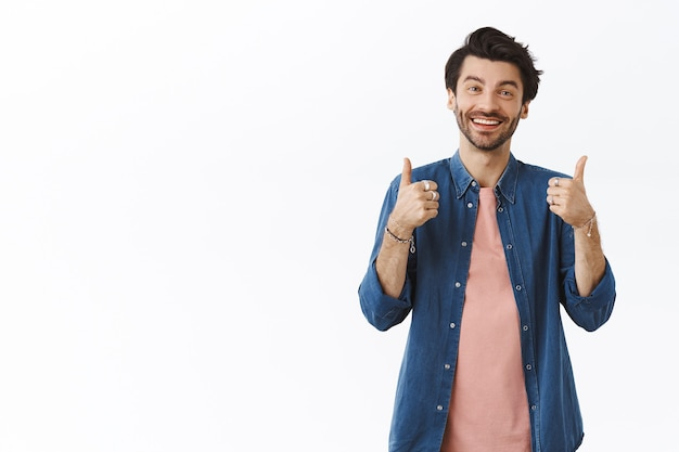 Homem caucasiano bonito e simpático, satisfeito e com uma roupa casual, mostrando o polegar para cima ao avaliar algo bom, sorrindo e acenando com a cabeça, dando feedback positivo, pensando que algo é excelente