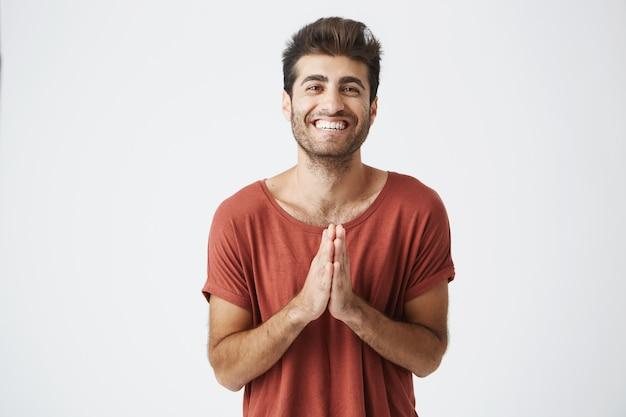 Homem caucasiano bonito em t-shirt vermelha sorrindo alegremente e batendo palmas de mãos surpreso com presente de aniversário de amigos. closeup retrato de cara com barba, compartilhando vibrações positivas.