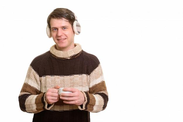Homem caucasiano bonito feliz usando protetores de ouvido de inverno e segurando