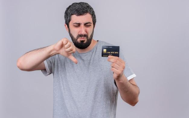 Homem caucasiano bonito jovem e desagradável mostrando e olhando para o cartão de crédito e mostrando o polegar para baixo, isolado no fundo branco com espaço de cópia