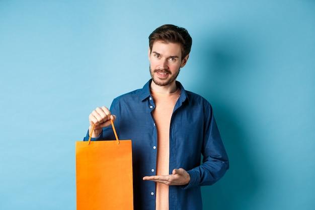 Homem caucasiano bonito mostrando a sacola de compras laranja e sorrindo, comprou um presente, de pé sobre um fundo azul. copie o espaço