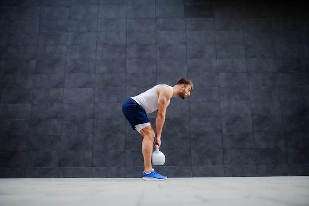 Homem caucasiano bonito muscular forte de bermuda e camiseta em pé ao ar livre e levantando o sino de chaleira. no fundo é parede cinza.