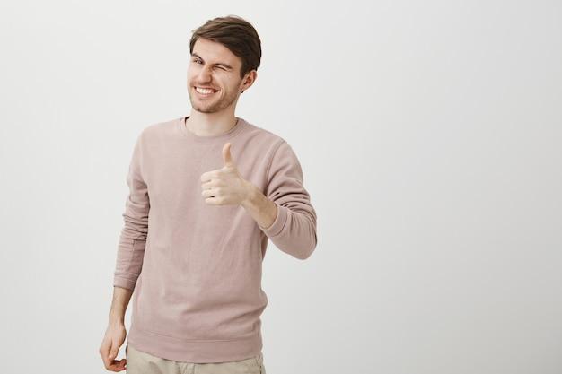 Homem caucasiano bonito satisfeito mostrando o polegar para cima