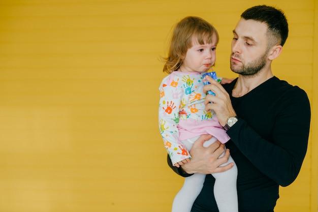 Homem caucasiano bonito, segurando na mão sua filha pequena sobre parede amarela