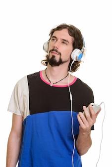 Homem caucasiano bonito segurando um celular e ouvindo música enquanto pensa