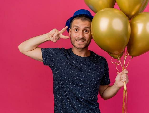 Homem caucasiano bonito sorridente com chapéu de festa azul segura balões de hélio e gestos sinal de mão da vitória isolado no fundo rosa com espaço de cópia