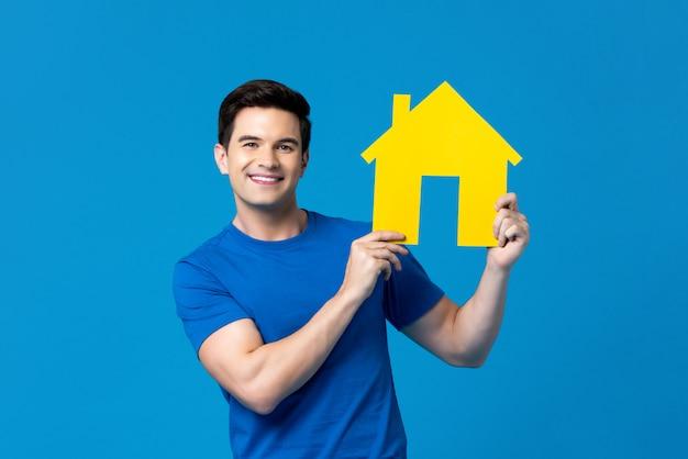 Homem caucasiano bonito sorridente segurando modelo de casa