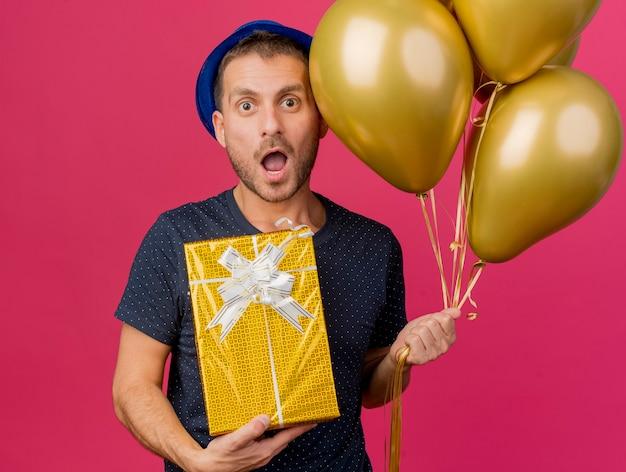 Homem caucasiano bonito surpreso com chapéu de festa azul segurando balões de hélio e uma caixa de presente isolada em um fundo rosa com espaço de cópia