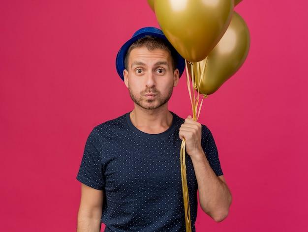 Homem caucasiano bonito surpreso com chapéu de festa azul segurando balões de hélio isolados em um fundo rosa com espaço de cópia