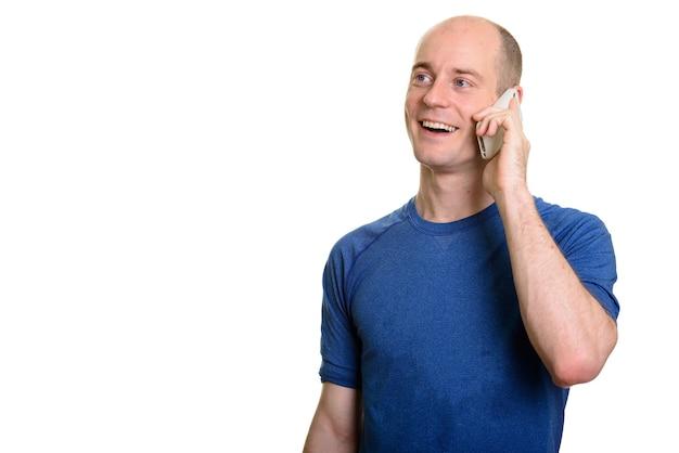 Homem caucasiano careca feliz e pensativo sorrindo e falando no celular