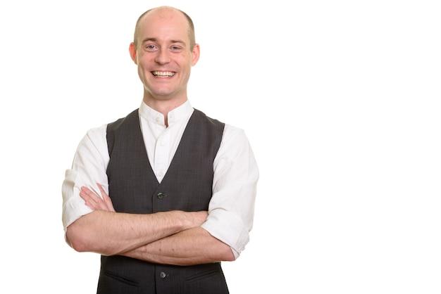 Homem caucasiano careca feliz sorrindo e vestindo colete com os braços cruzados