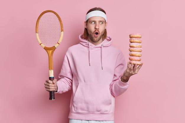 Homem caucasiano chocado com expressão de espanto no rosto, pausa durante o jogo de tênis, segura raquete e pilha de donuts leva vida ativa