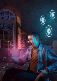 Homem caucasiano chocado e triste usando gadgets para obter informações sobre a pandemia de coronavírus