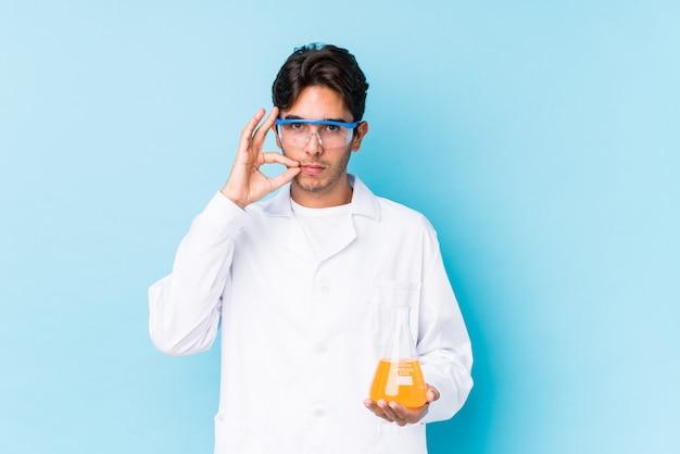 Homem caucasiano científico novo isolado com os dedos nos lábios, mantendo um segredo.