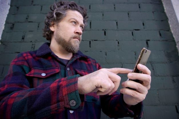 Homem caucasiano com barba ao ar livre segurando o celular nas mãos na parede de tijolo azul