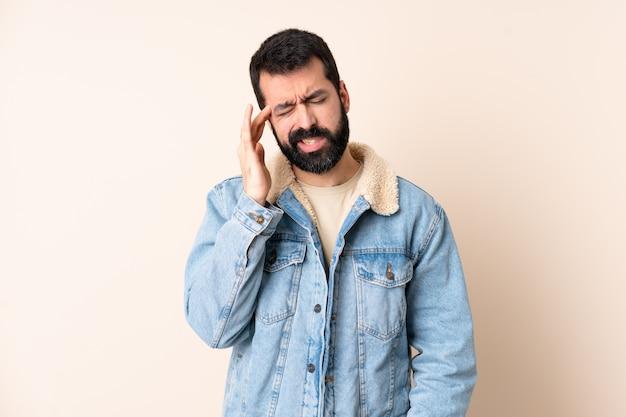 Homem caucasiano com barba ao longo da parede com dor de cabeça