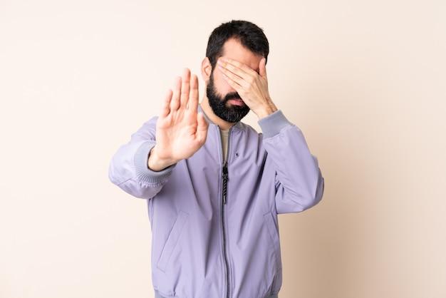 Homem caucasiano, com, barba, desgastar, um, casaco, sobre, isolado, fazendo, parada, gesto, e, cobrindo rosto