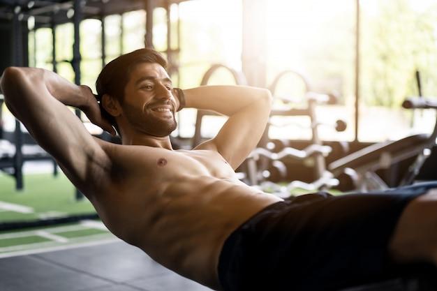 Homem caucasiano com barba e sem camisa exercitando, fazendo um abdominais no banco no ginásio ou no clube de fitness.