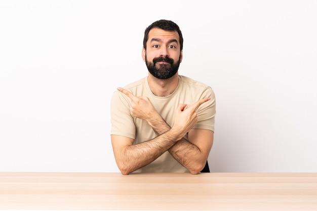 Homem caucasiano com barba em uma mesa apontando para as laterais, tendo dúvidas.