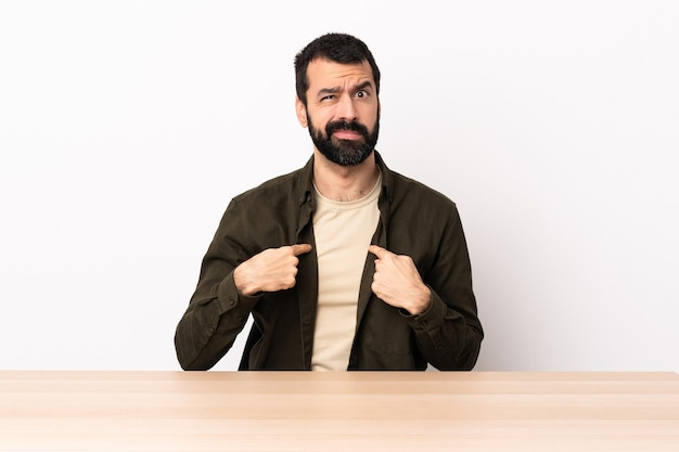 Homem caucasiano com barba em uma mesa apontando para si mesmo.