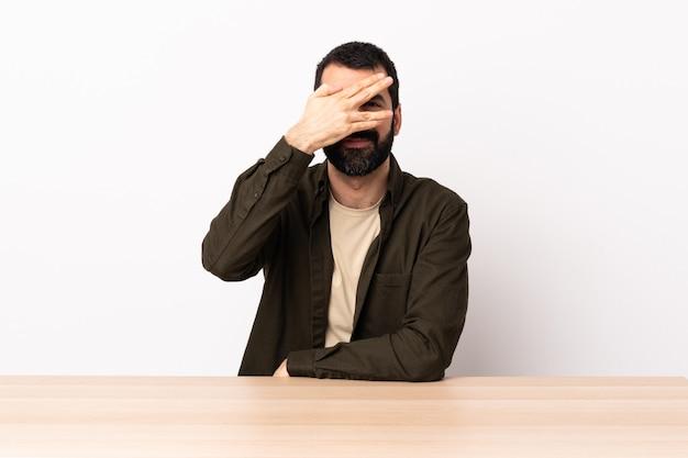 Homem caucasiano com barba em uma mesa coning olhos pelas mãos e sorrindo.