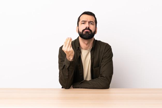 Homem caucasiano com barba em uma mesa fazendo gesto italiano.