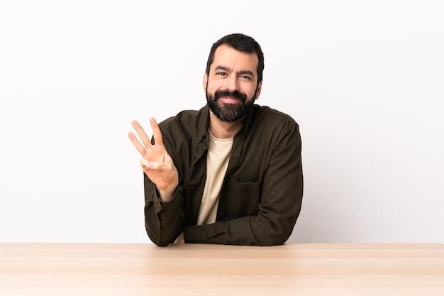 Homem caucasiano com barba em uma mesa feliz e contando três com os dedos