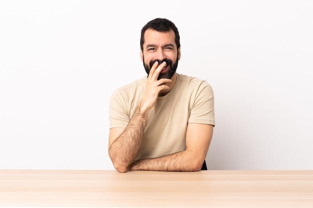 Homem caucasiano com barba em uma mesa feliz e sorridente, cobrindo a boca com a mão.